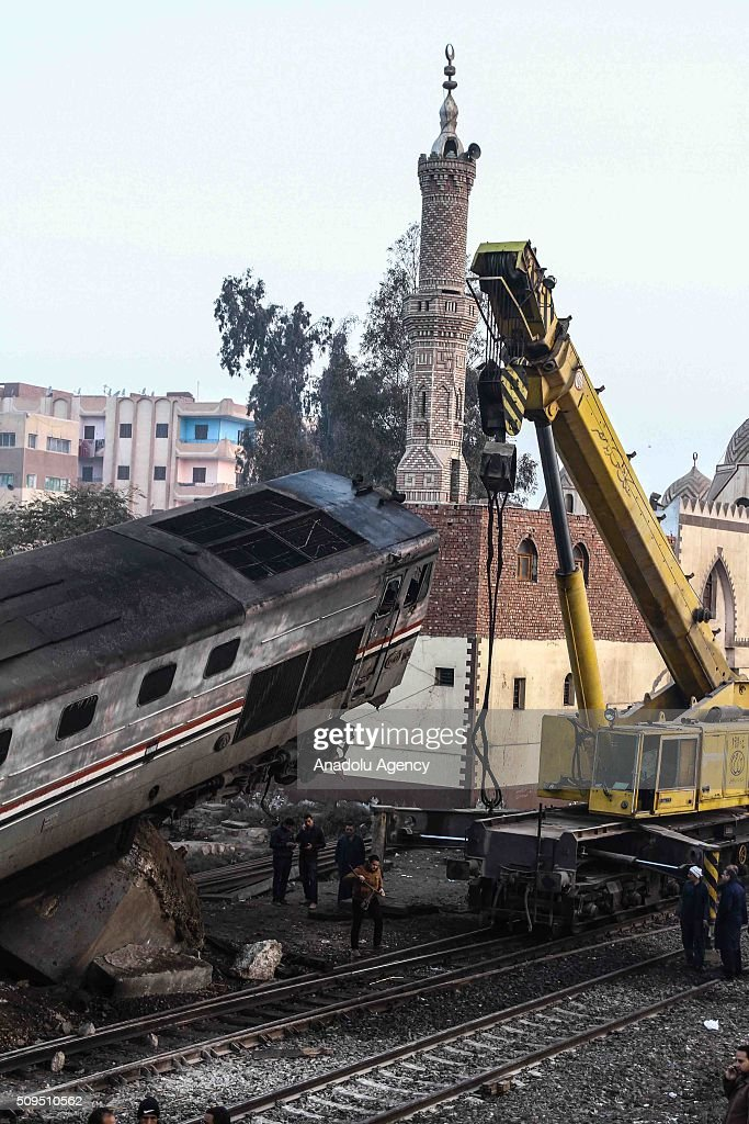 Railway workers and rescue team members inspect the crash site after a passenger train hit a concrete barrier on the railway in Beni Suef, Egypt on February 11, 2016. Numbers of people wounded due to accident, reported.