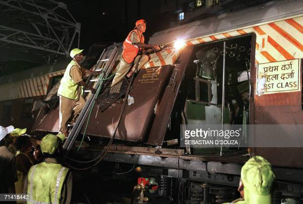 Railway workers cut through a portion of the first class compartment of a local train which was ripped open by a bomb blast at Khar Mumbai late 11...