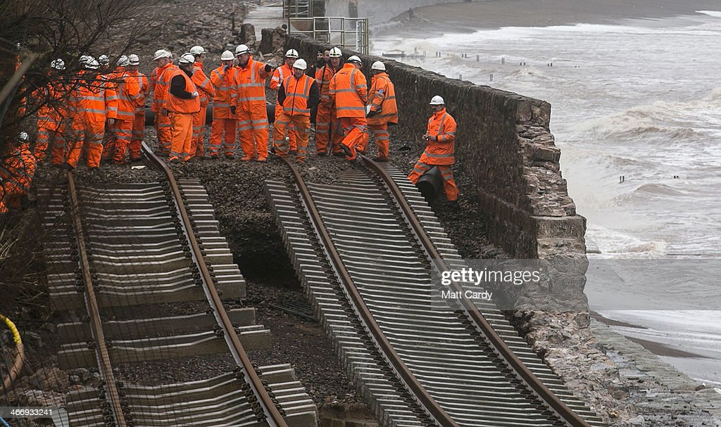 Railway workers inspect the main Exeter to Plymouth railway line that has been closed due to parts of it being washed away by the sea at Dawlish on February 5, 2014 in Devon, England. With high tides combined with gale force winds and further heavy rain, some parts of the UK are bracing themselves for more flooding.