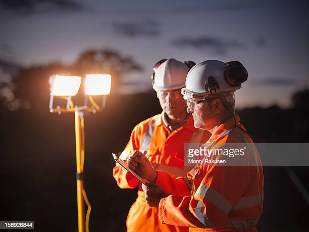 Railway workers making notes at night with floodlight in background