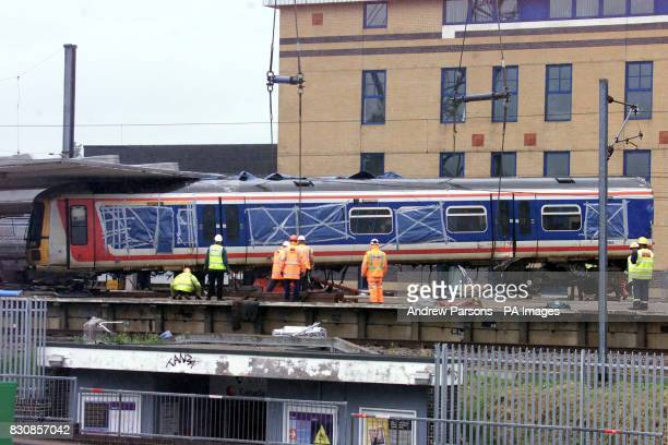 Railway workers remove a carriage from where it was lying across two platforms at Potters Bar station north of London The lift put on hold because of...