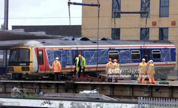 Railway workers remove a carriage from where it was lying across two platforms at Potters Bar station north of London The lift was put on hold...