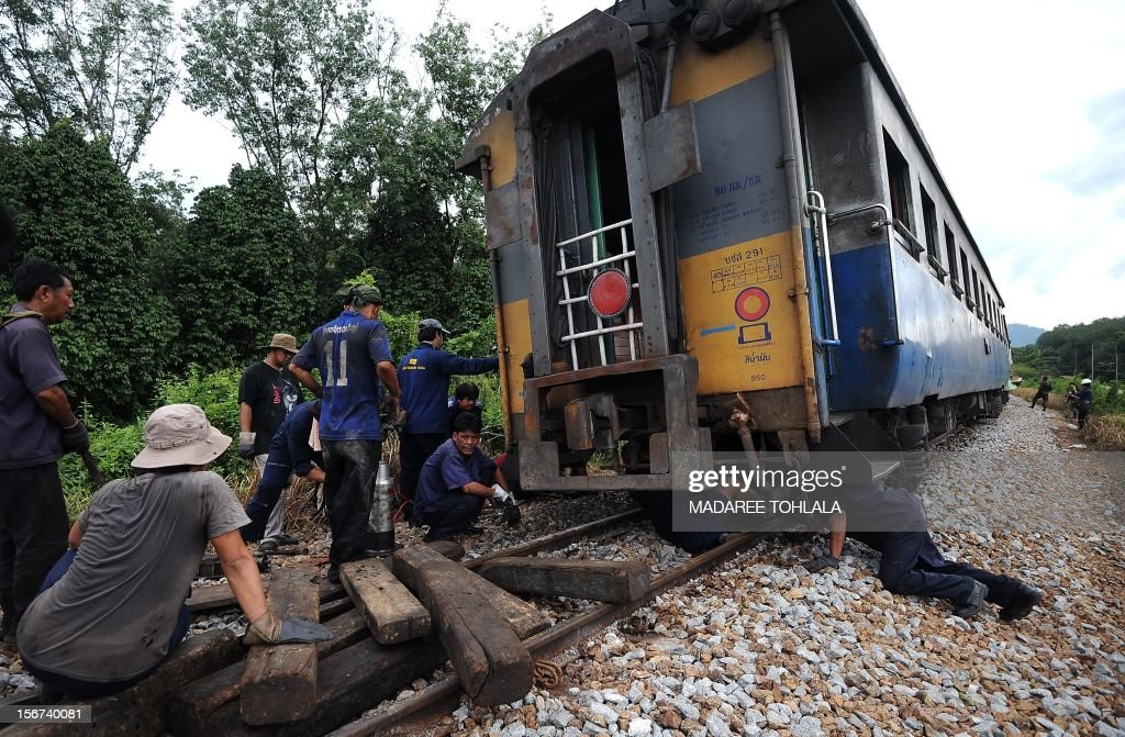 Railway workers repair railway tracks after a bomb exploded by suspected separatist milltants in Thailand's restive southern province of Narathiwat on November 20, 2012. An insurgency calling for greater autonomy has racked Thailand's far south near the border with Malaysia since 2004. It has claimed more than 5,300 lives, both Buddhist and Muslim, with near-daily bomb or gun attacks. AFP PHOTO/MADAREE TOHLALA