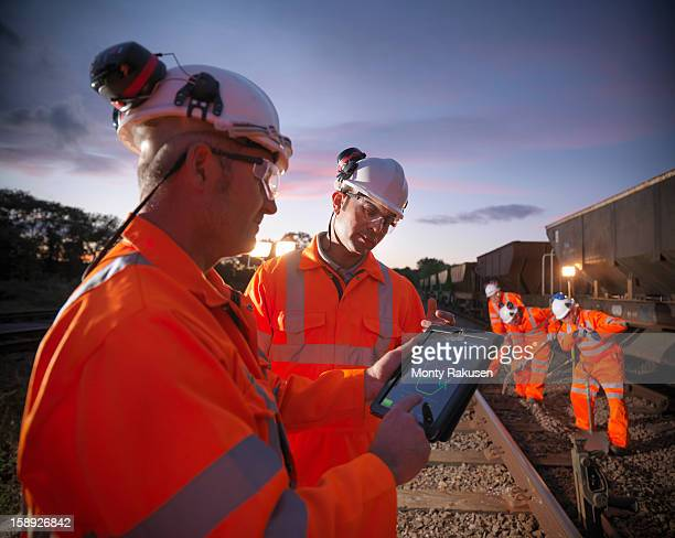 Railway workers using digital tablet to view work details on railway tracks