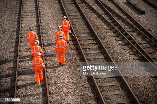 Railway workers walking along railway tracks