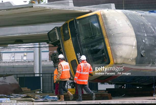 Railway workers watch as further attempts are made to remove a railway carriage from Potters Bar station north of London The lift was put on hold...