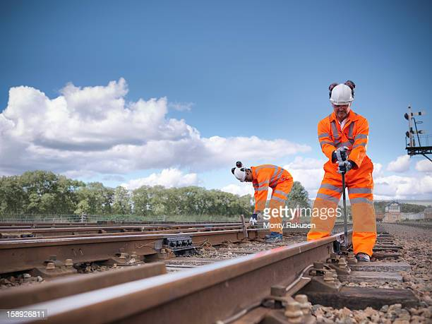 Railway workers wearing high visibility clothing repairing railway track