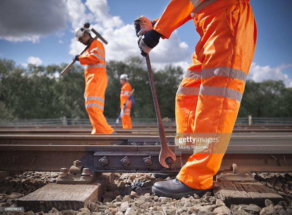 Railway workers wearing high visibility clothing repairing railway track side view