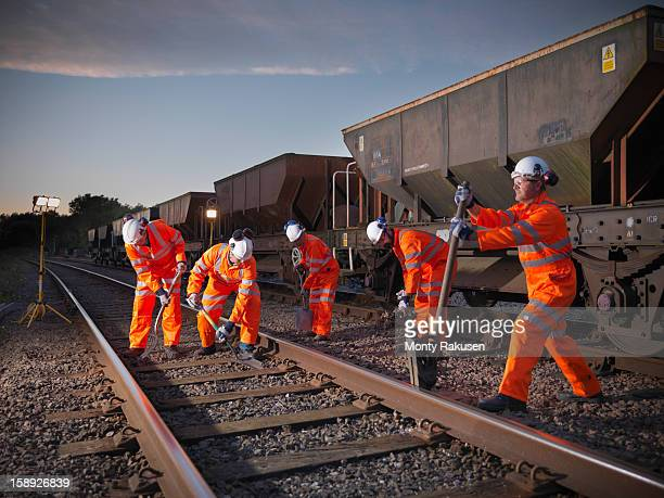 Railway workers working on railway tracks at night