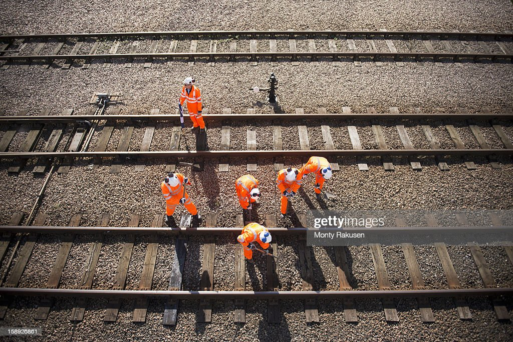 Railway workers working on railway tracks, overhead view