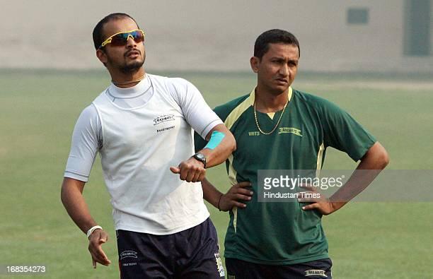 Railways players Murli Kartik and Sanjay Bangar during a practice session at Karnail Singh Stadium on October 31 2010 in New Delhi India