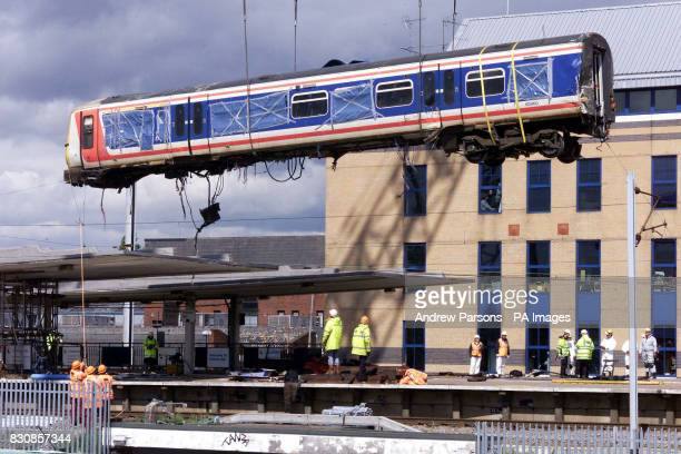 Railworkers guide the train carriage over the roof from where it was lying across two platforms at Potters Bar station north of London as it is crane...