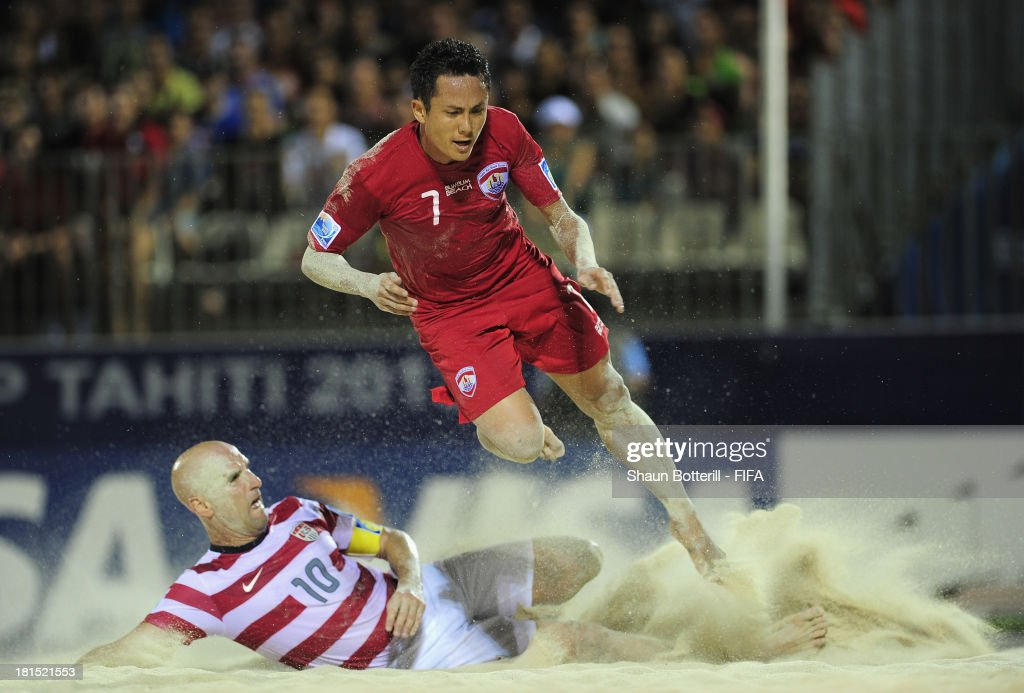 Raimana Li Fung Kuee of Tahiti is tackled by Francis Farberoff of USA during the FIFA Beach Soccer World Cup Tahiti 2013 Group A match between USA and Tahiti at the Tahua To'ata stadium on September 21, 2013 in Papeete, French Polynesia.