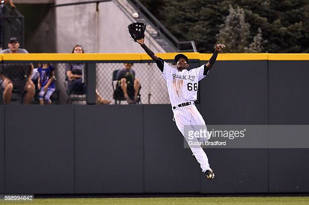 Raimel Tapia of the Colorado Rockies makes a leaping catch in the ninth inning of a game against the Arizona Diamondbacks at Coors Field on September...