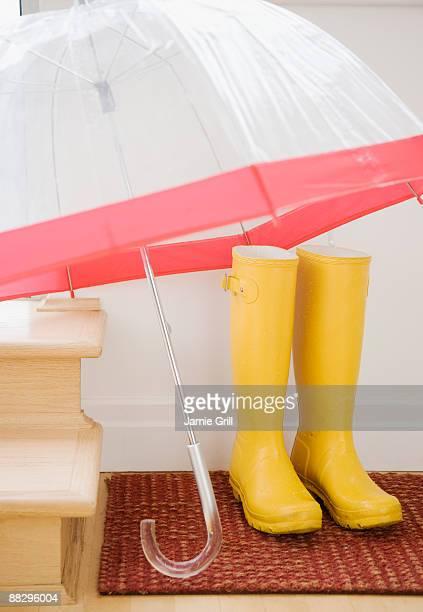 Rain boots and umbrella drying indoors
