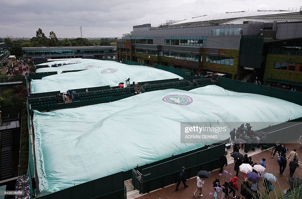 Rain covers are drawn over the outside courts as rain halts the start of the third day of the 2016 Wimbledon Championships at The All England Lawn Tennis Club in Wimbledon, southwest London, on June 29, 2016. / AFP / ADRIAN