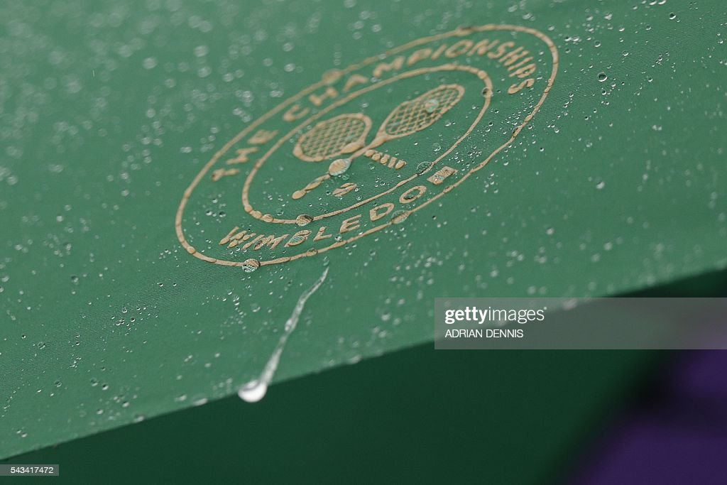 Rain dribbles down the side of an umbrella after rain stopped play on the second day of the 2016 Wimbledon Championships at The All England Lawn Tennis Club in Wimbledon, southwest London, on June 28, 2016. / AFP / ADRIAN