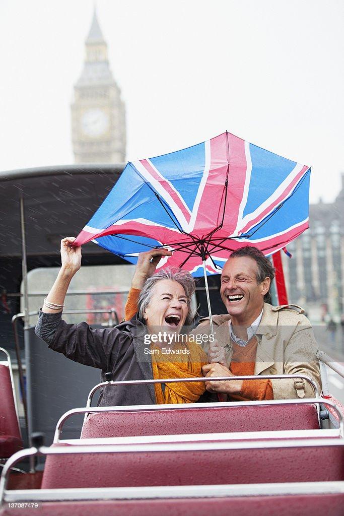 Rain falling on couple with British Flag umbrella on double decker bus