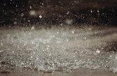 Rain falling on the asphalt of the street