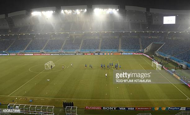 Rain falls during Greece's team training session at the Dunas Arena in Natal on June 18 one day before their Group C 2014 FIFA World Cup match...
