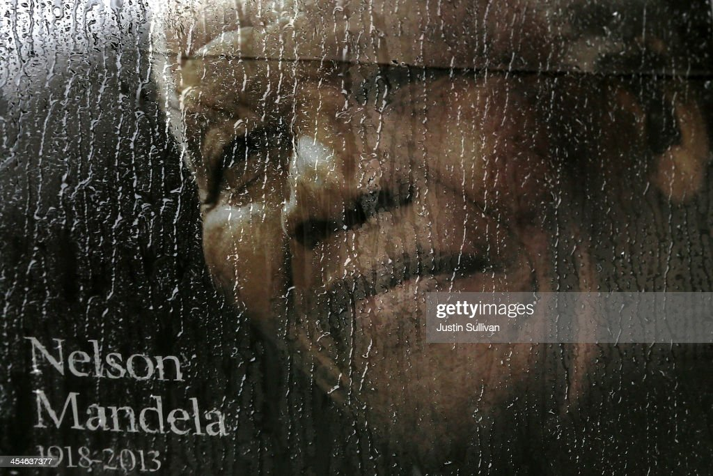 Rain falls on a poster of Nelson Mandela sitting in the window of a bus outside of Ellis Park before a telecast of the Nelson Mandela memorial service on December 10, 2013 in Johannesburg, South Africa. Over 60 heads of state have travelled to South Africa to attend a week of events commemorating the life of former South African President Nelson Mandela. Mr Mandela passed away on the evening of December 5, 2013 at his home in Houghton at the age of 95. Mandela became South Africa's first black president in 1994 after spending 27 years in jail for his activism against apartheid in a racially-divided South Africa.
