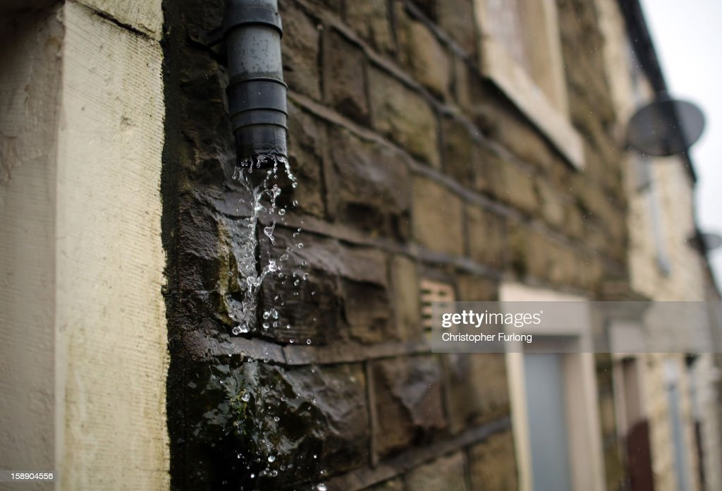 Rain pours down the walls of empty former council houses in the Lancashire town of Accrington as they wait to be modernised by private developers on January 3, 2013 in Accrington, England. There are estimated to be 850,000 empty homes in the United Kingdom even though local councils still have long waiting lists for housing. The terraced houses were due to be rejuvenated by Accrington council but the project was put on hold when the government cut a housing regeneration project.