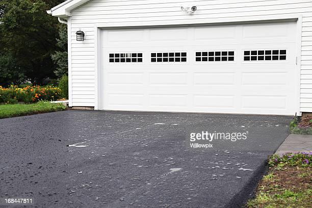 Lluvia Puddles en la nueva entrada en residencial casa asfalto