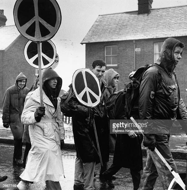 Rain soaked CND marchers carrying their antinuclear logos at Aldermaston