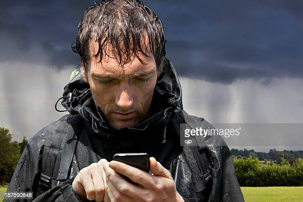 Rain Soaked Hiker Consults Touchscreen GPS Smartphone