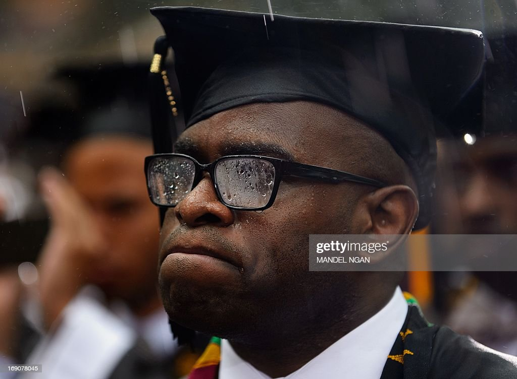 A rain soaked member of the 2013 graduating class listens to US President Barack Obama deliver the commencement address during a ceremony at Morehouse College on May 19, 2013 in Atlanta, Georgia. AFP PHOTO/Mandel NGAN