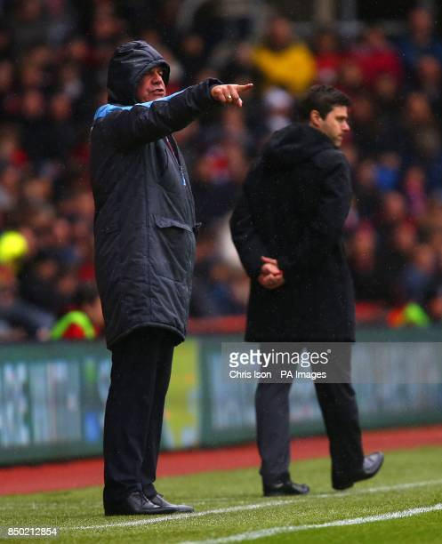 A rain soaked West Ham United manager Sam Allardyce gives instructions from the touchline