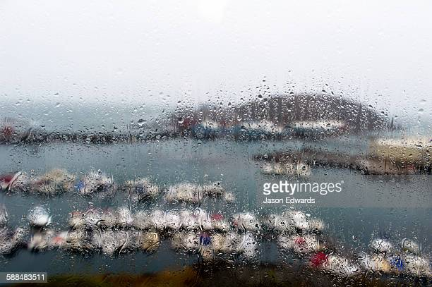 A rain storm lashing a window overlooking a fishing boat harbor.