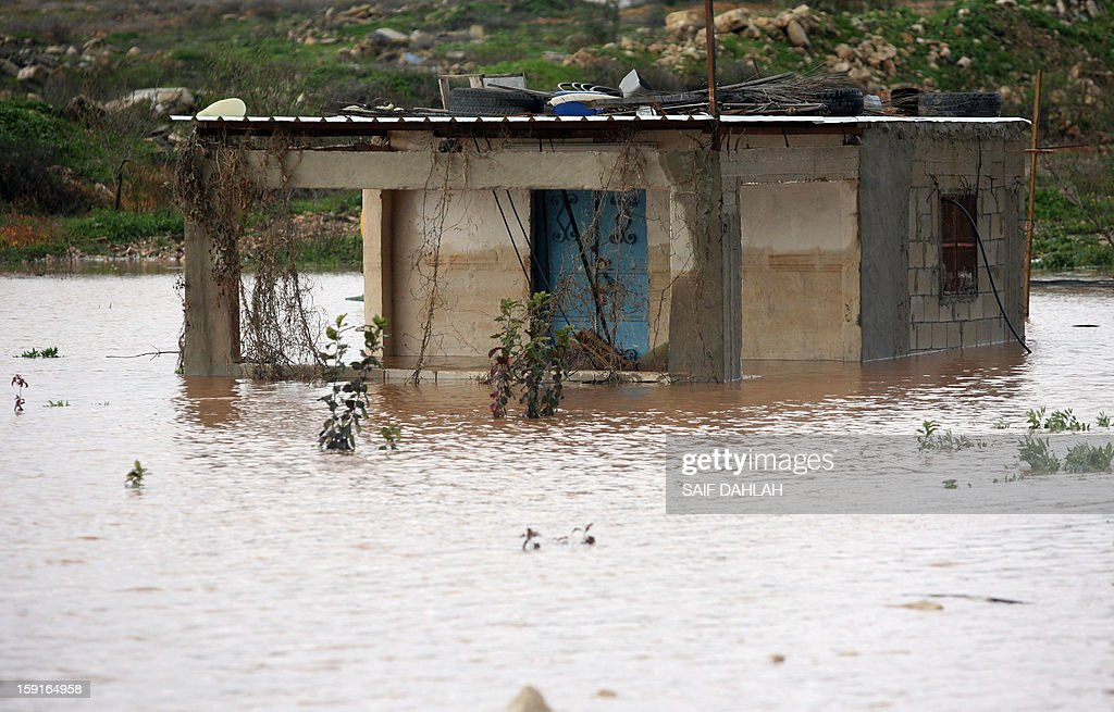 Rain water flood a house on the outskirts of the village of Qabatiya, in the Israeli occupied West Bank near the northern city of Jenin, on January 9, 2013, as rain and snow engulfs the Levant.