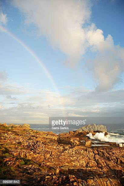 Rainbow and waves breaking on rocky shore at sunset, Hermanus, South Africa