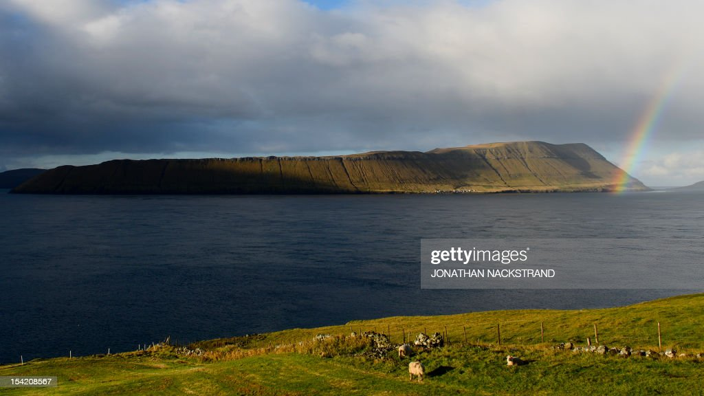 A rainbow appears above the Hestur island on October 16, 2012, Faroe Islands. The Faroe Islands are known for its fishing and sheep farming as the main industries.