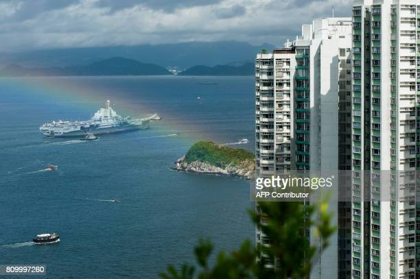 A rainbow appears as China's aircraft carrier Liaoning sails past residential tower blocks in Hong Kong on July 7 2017 China's national defence...
