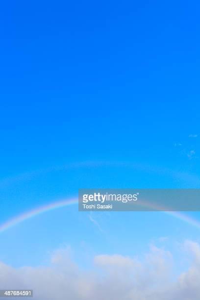 Rainbow appears over cloud at blue sky.
