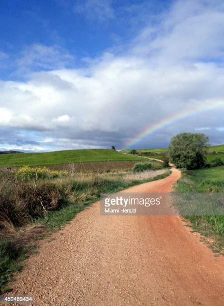 A rainbow beckons down the path of the The Alto de Perdon in May 2014 along the Camino de Santiago de Compostela trail in Spain The popularity of...