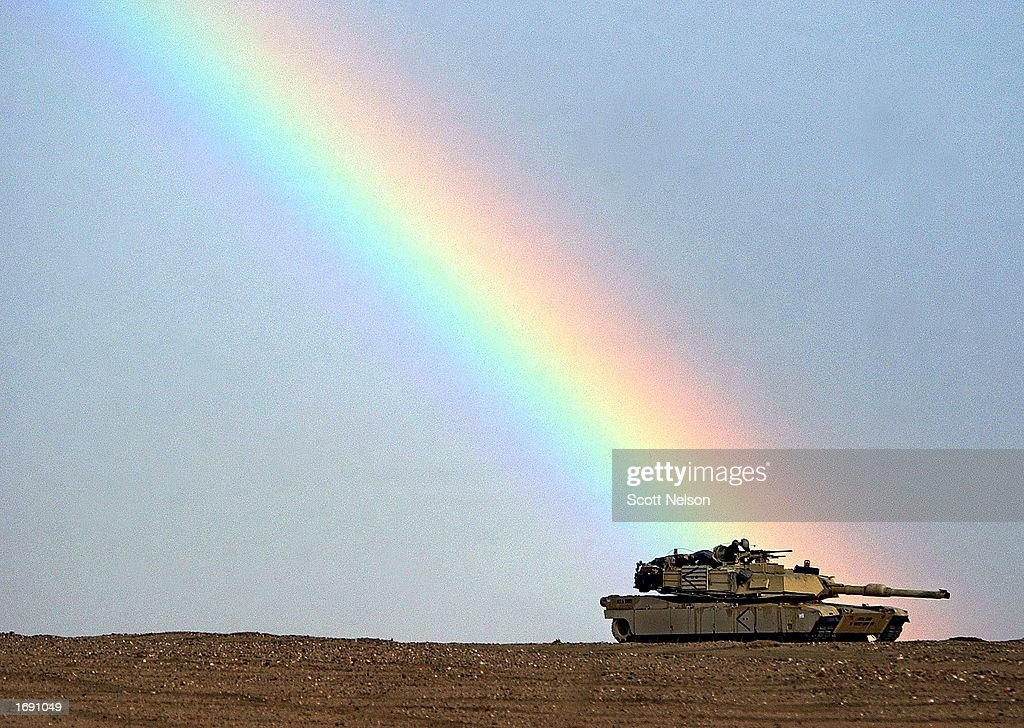 A rainbow breaks over the position of an M1/A1 Abrams tank from the Charlie company 464 Armored Battalion during task force manuevers December 17...