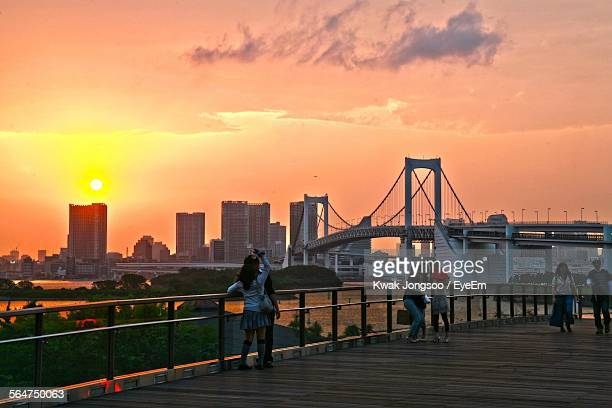 Rainbow Bridge During Sunset With City In Background