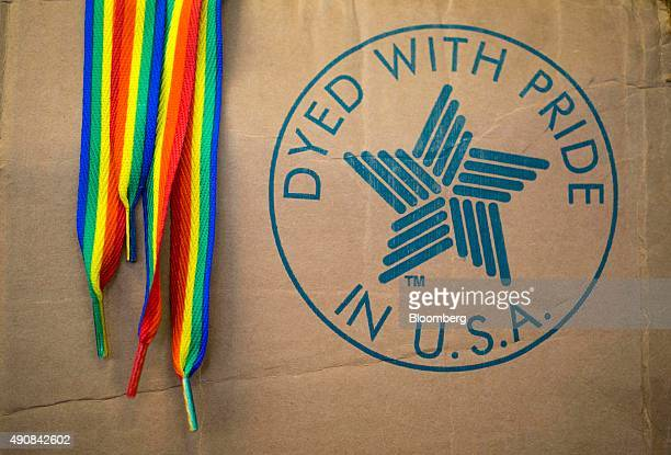 Rainbow colored shoelaces hang next to a 'Dyed With Pride In USA' stamp on the side of a box in the packaging area at the Sole Choice Inc...