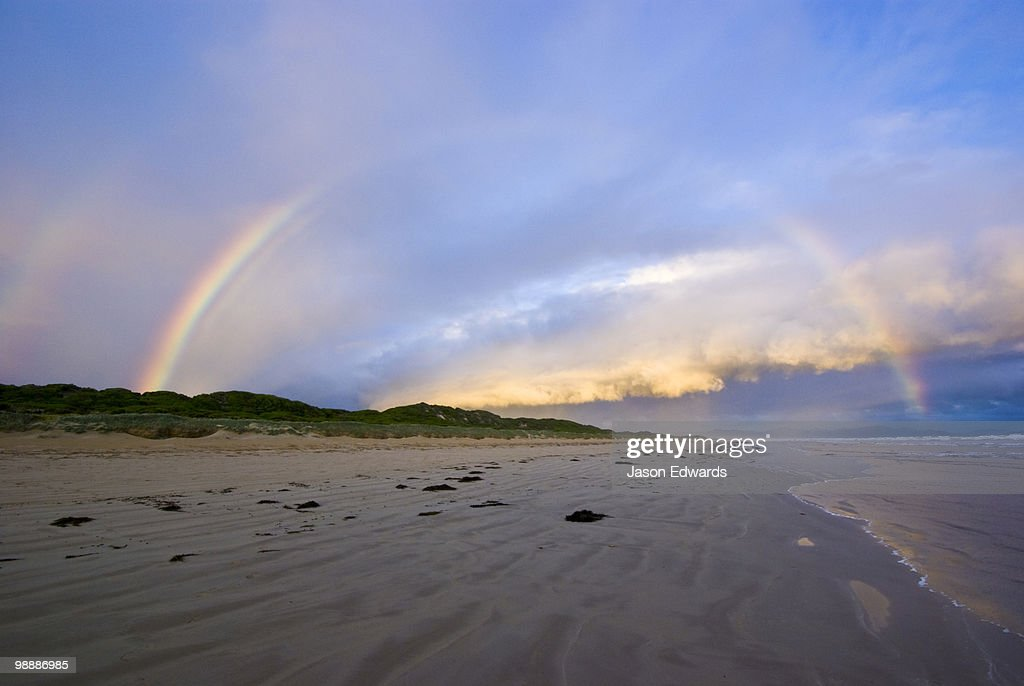 A rainbow crests a storm front over a wide deserted beach at twilight. : Stock Photo