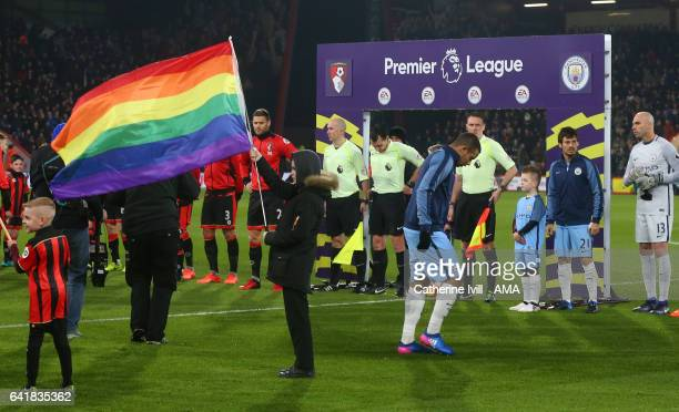 A rainbow flag is held up next the Premier League Board as the players line up during the Premier League match between AFC Bournemouth and Manchester...