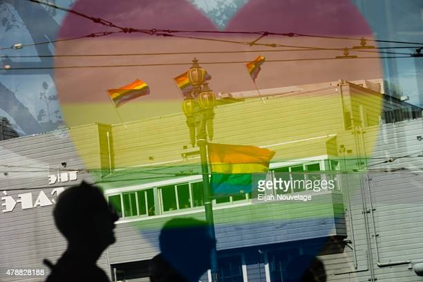 Rainbow flags and reverlers are seen in the reflection of a store window display during a gay pride celebration on June 27 2015 in San Francisco...