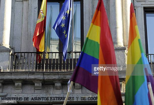 Rainbow flags fly in front of European and Spanish flags during a protest against homophobia and repression against gays in Russia outside the...