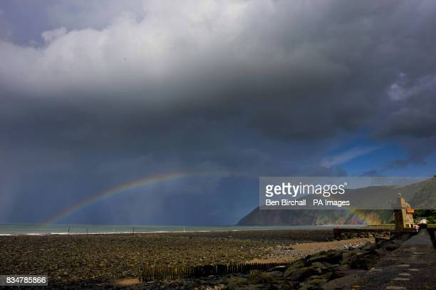 A rainbow forms during heavy rain and showers at Lynmouth Devon
