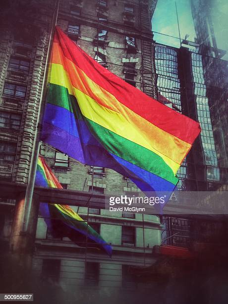 Rainbow gay pride flag hanging on building At West 54th St and Broadway New York City