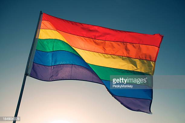 Rainbow Gay Pride Flag Waving Backlit by Bright Sun Sky