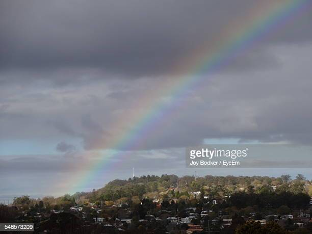 Rainbow In Cloudy Sky Over Townscape
