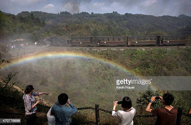 A rainbow is seen as Chinese tourists take pictures of a coal powered engine letting off steam on March 29 2015 near the village of Bagou Sichuan...